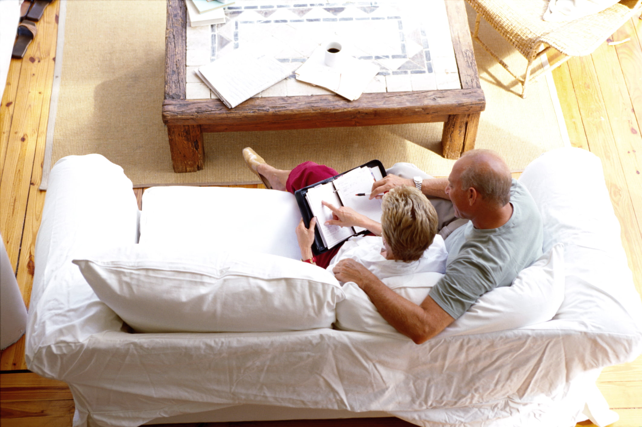 high angle view of a mature couple reading on the couch together